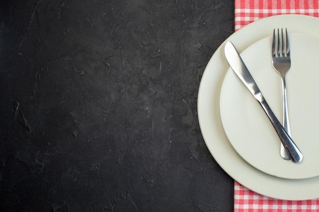 여유 공간이 있는 검정색 배경의 왼쪽에 있는 빨간색 벗겨진 수건에 있는 흰색 빈 접시에 스테인리스 칼 붙이 세트의 오버 헤드 보기