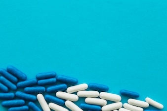 Overhead view of sweet candy capsules on cyan background