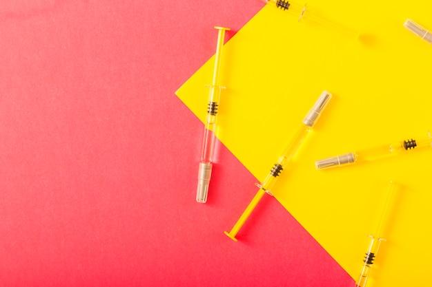 노란색과 빨간색 배경 위에 주사기의 오버 헤드보기