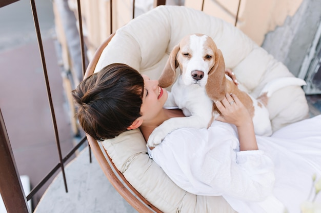 Вид сверху загорелой брюнетки, смотрящей с улыбкой на сонную собаку бигля, сидящую рядом