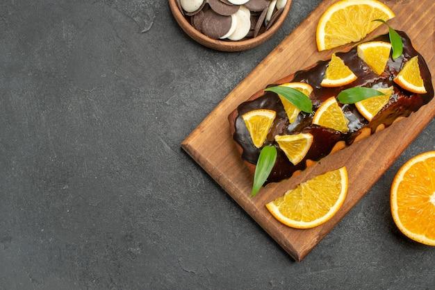 맛있는 케이크의 오버 헤드보기는 블랙 테이블에 커팅 보드에 비스킷과 오렌지를 잘라