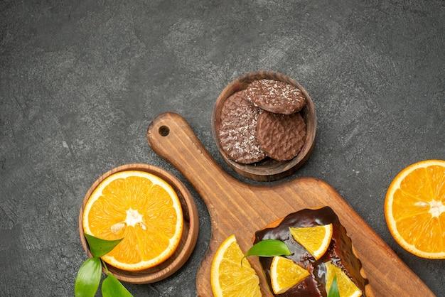 맛있는 케이크의 오버 헤드보기는 어두운 테이블에 커팅 보드에 비스킷으로 오렌지를 잘라냅니다.