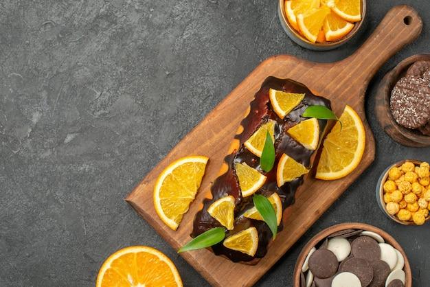 Вид сверху на вкусные торты целиком и нарезанные апельсины с печеньем на разделочной доске на темном столе