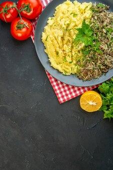 Вид сверху вкусного ужина с мясным пюре на тарелке и помидорами со стеблями упавшего перца бутылки масла на черном фоне со свободным пространством