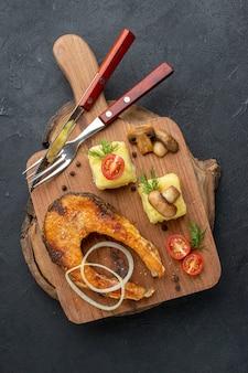 まな板カトラリーのおいしい揚げ魚とキノコのトマトグリーンの俯瞰図黒の表面にコショウをセット