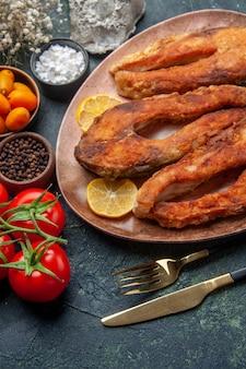 茶色のプレートにおいしい揚げ魚とレモンスライスの俯瞰図トマトキンカン、空きスペースのあるミックスカラーテーブル