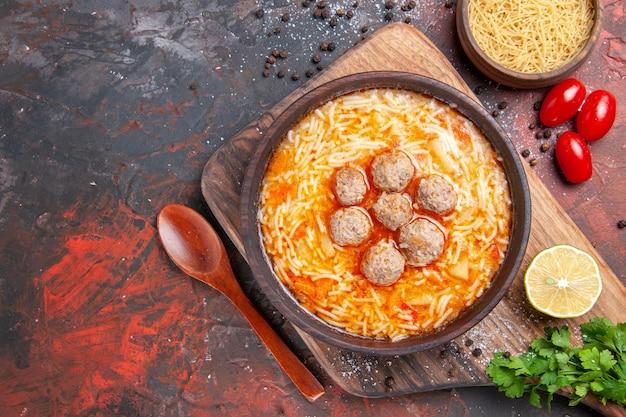 レモンの木製パスタに麺が乗ったおいしいミートボールスープの俯瞰図暗いテーブルの上の緑の束