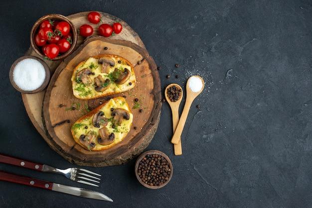 黒の背景に設定された木の板カトラリーにキノコトマト塩とおいしいおやつの俯瞰図