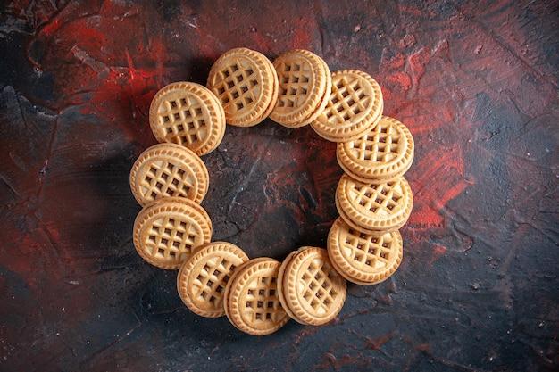여유 공간이 있는 혼합 색상 배경에 둥근 형태로 배열된 맛있는 설탕 쿠키의 오버헤드 보기