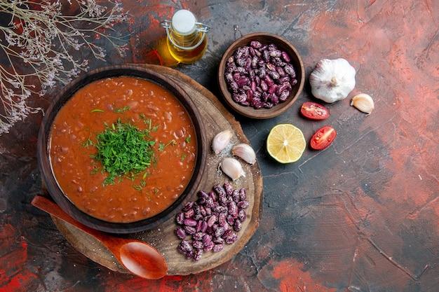 木製のまな板とオイルボトルレモンのトマト石鹸豆にんにくスプーンの俯瞰図
