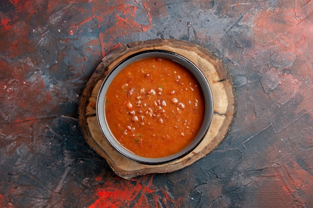 混合色のテーブルの茶色の木製トレイに青いボウルのトマトスープの俯瞰図