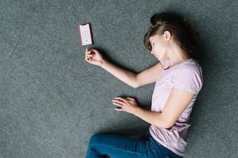 Overhead view of unconscious woman lying near cell phone on carpet