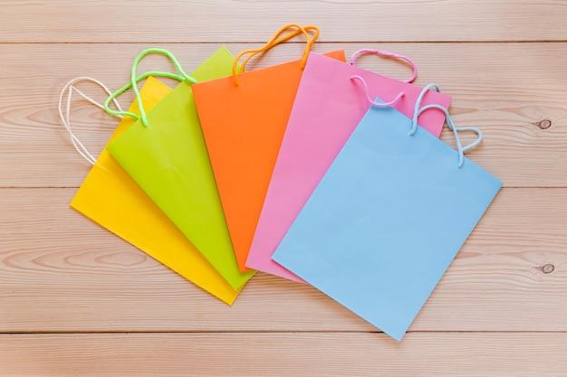 나무 책상에 다양 한 다채로운 쇼핑백의 오버 헤드보기