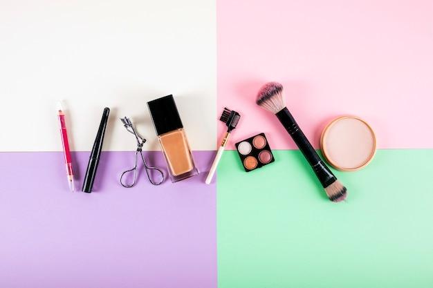 Верхний вид различных косметических продуктов на многоцветном фоне