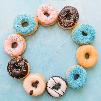 Overhead view of various fresh donuts forming circular frame