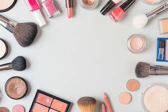 Overhead view of various makeup products forming circular shape on white background