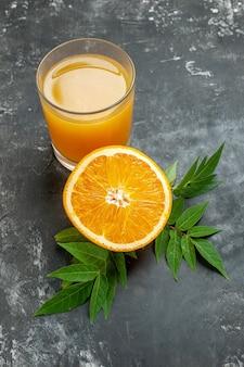 회색 배경에 잎이 있는 신선한 오렌지와 주스를 자른 비타민 소스의 머리 위
