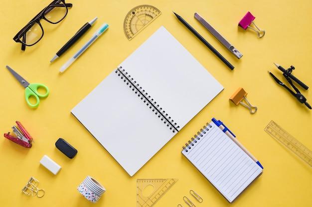 黄色い背景の鮮明な文房具のオーバーヘッドビュー