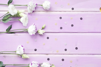 Overhead view of white flowers on pink wooden backdrop