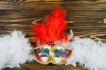 Overhead view of white masquerade carnival mask with boa feather on wooden table