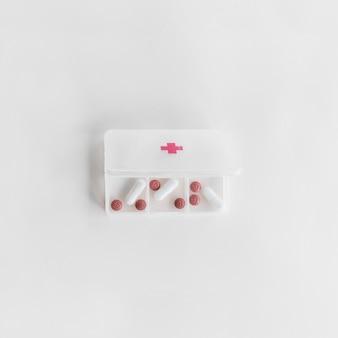 Вид сверху белый пластиковый органайзер таблетки на белом фоне