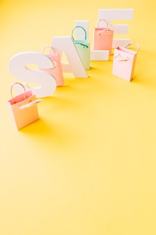 노란색 배경에 작은 분홍색 쇼핑백과 흰색 판매 단어의 오버 헤드보기