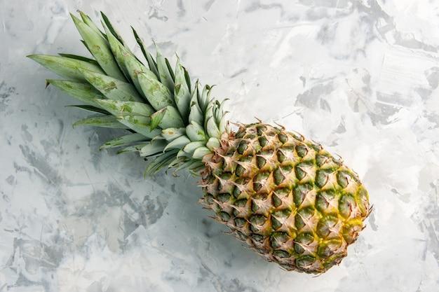 Вид сверху на весь свежий золотой ананас на мраморной поверхности