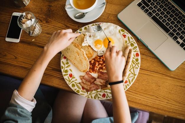 Накладные зрения женщины, едят здоровый завтрак в кафе