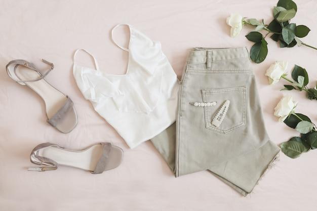 여자의 캐주얼 봄 여름 복장 청바지 흰 블라우스 샌들과 꽃의 꽃다발의 오버 헤드보기