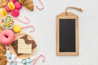 Overhead view of wooden slate tag and sweet foods on white background