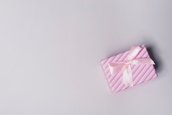 Overhead view of wrapped gift box with pink bow on gray background