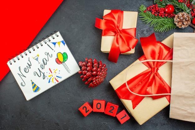 Вид сверху на блокнот рождественского настроения с новогодними рисунками, хвойными шишками и номерами подарочных еловых веток на темном столе