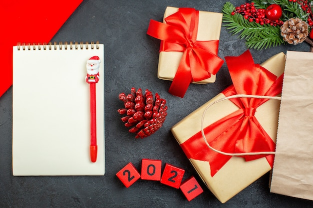 Вид сверху на блокнот рождественского настроения с ручкой из хвойных шишек и числами подарочных еловых веток на темном столе