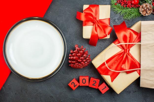 Вид сверху на рождественскую тарелку хвойных шишек и подарочные еловые ветки на темном столе