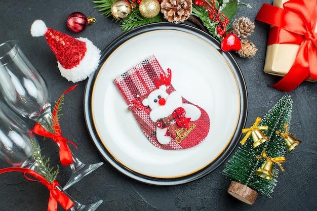 Вид сверху на рождественский носок на обеденной тарелке рождественская елка еловые ветки хвойные шишки подарочная коробка шляпа санта-клауса упавшие стеклянные кубки на черном фоне