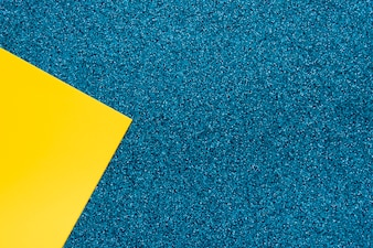 Overhead view of yellow cardboard paper on blue surface