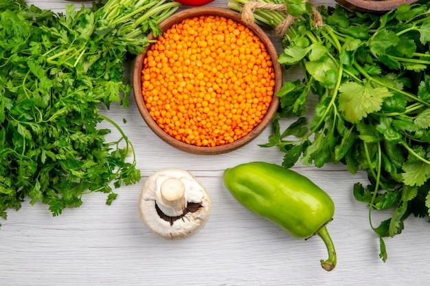白いテーブルの上の緑のキノコの黄色いレンズ豆の束の俯瞰図