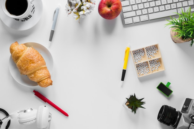 An overhead view of an office stationeries with baked croissant and apple on white desk