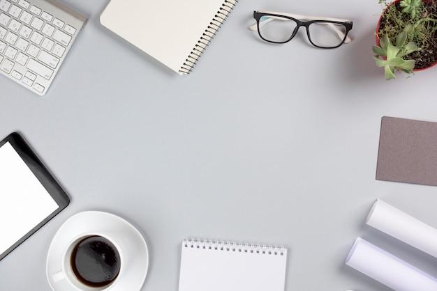 Una vista aerea degli articoli per ufficio con la tazza di caffè contro fondo grigio