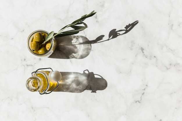 Overhead view of olive jar with twig and oil on white marble background
