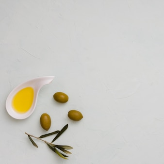 An overhead view of olive; leaves and oil on white concrete background