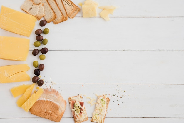 An overhead view of olives; cheese slice and bread on white wooden table