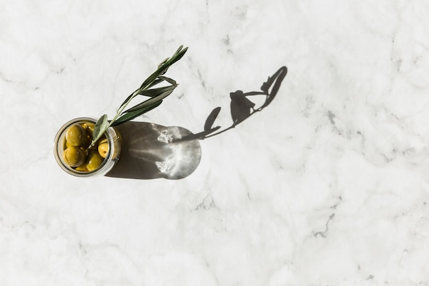 Overhead view of olives jar with twig on marble background