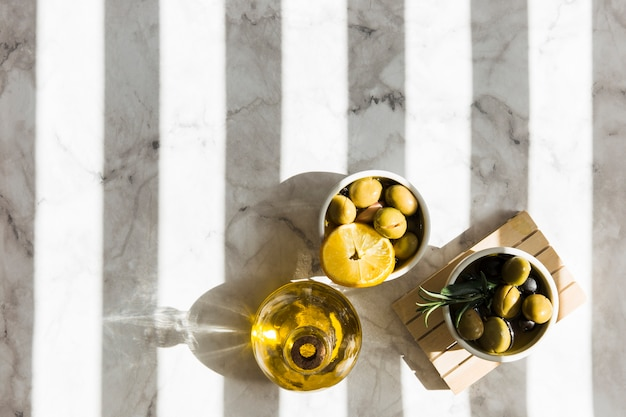 Overhead view of olives with lemon slice and rosemary her with oil bottle