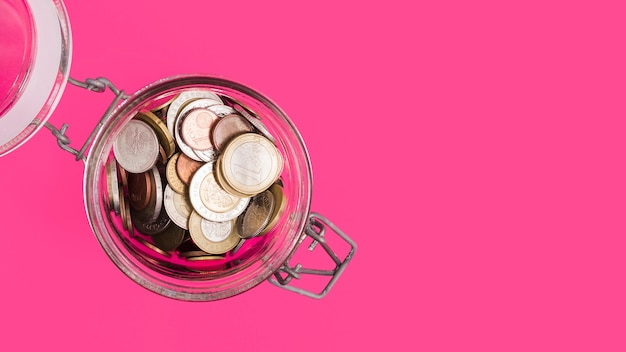 An overhead view of an open glass jar with many coins on pink backdrop