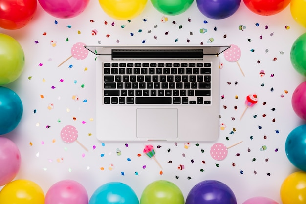 An overhead view of an open laptop decorated with confetti; prop and colorful balloons on white backdrop