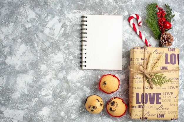 Overhead view of open notebook and beautiful christmas packed gift with love inscription small cupcakes and fir branches decoration accessories conifer cone on ice surface