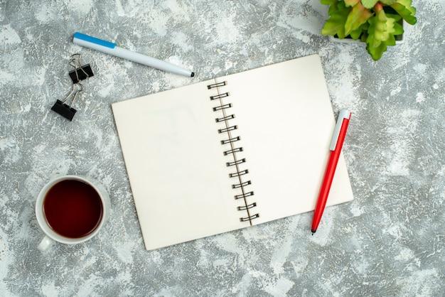 Vista dall'alto di un quaderno a spirale aperto con due penne e una tazza di vaso di fiori da tè su sfondo grigio