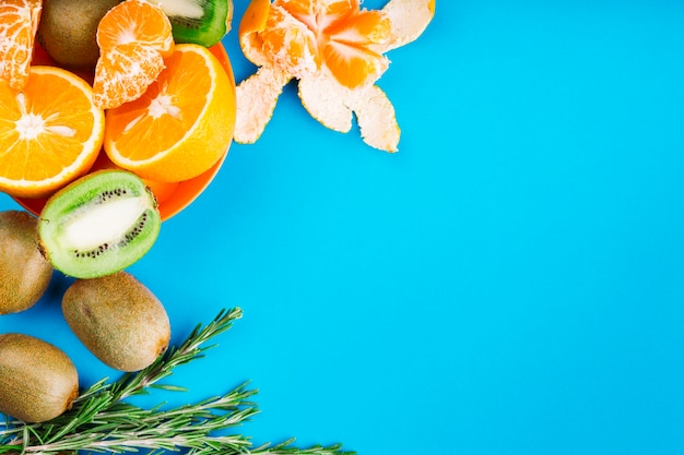 An overhead view of oranges; kiwi and rosemary on blue backdrop