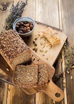 An overhead view of organic bread and energy bar on chopping board